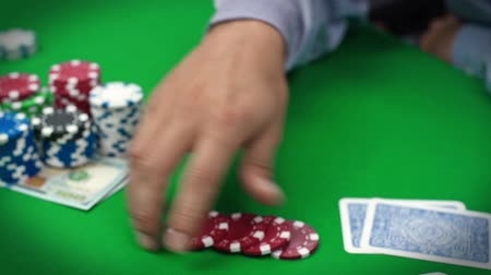 покер : poker player touches the chips in hand Стоковые видеозаписи