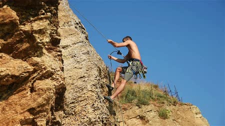 manges : Rock Climber Climbing A Rope From A Cliff. Slow Motion Effect Stock Footage