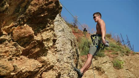 manges : Extreme Rock Climber Climbing A Rope From A Cliff