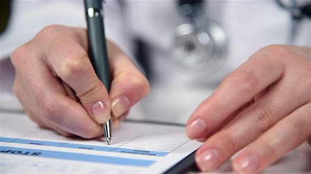 boletim : Woman Therapist Filling Medical Form Patient Sitting In Clinic. Close Up Stock Footage