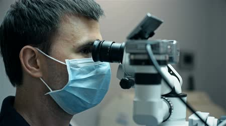 устройство : Dentist Is Looking Through Dental Microscope With Camera. Close Up