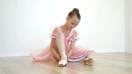 bale : Little Ballerina In Pink Dress And Pointe Shoes Is Dancing In Room. Slow Motion Effect