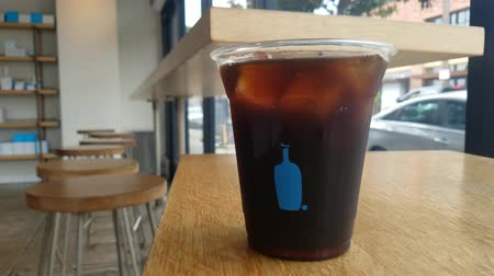 mal cheiroso : Los Angeles, SEP 17: A cup of cold brew coffee and interior view of The famous Blue bottle store on SEP 17, 2017 at Los Angeles, California, U.S.A. Stock Footage