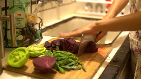 реальное время : Chopping garlic green and red beets in a chopping board at home, Los Angeles