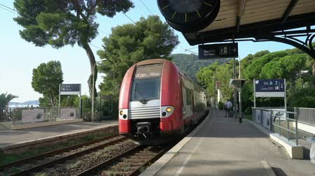 stopping : Exterior view of the Eze Train Station with a train entering the platform near Nice, France Stock Footage