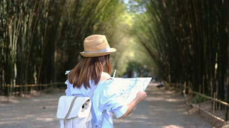 Young woman traveler searching direction on location map while traveling