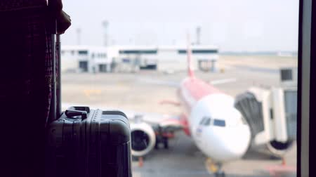 Young woman traveler with luggage looking at the airplane at the airport, Travel concept