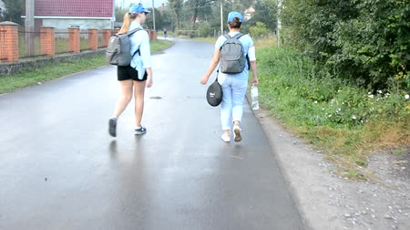 plecak : Two girls tourists go on the road - rear view. Wideo