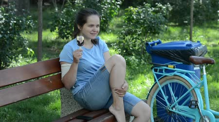 oturur : A girl sits in the park and eats ice cream. Stok Video