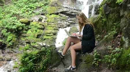 ebook : The girl works behind a laptop in nature on the background of a waterfall. Stock Footage