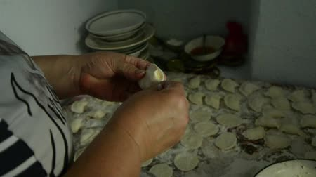 клецка : A woman makes a lot of dumplings with cottage cheese.