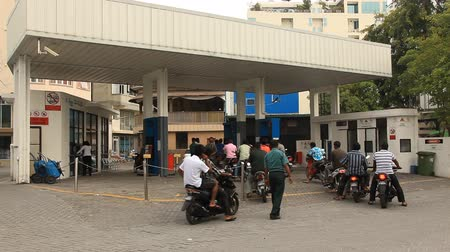 necessity : Male, Maldives - December, 2012: owners of motorcycles buy petrol on petrol station. Male, Maldives.