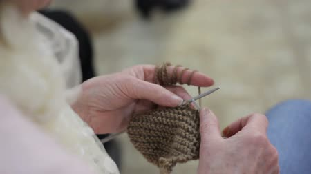 pessoal : Womans hands are knitting clothes of wool
