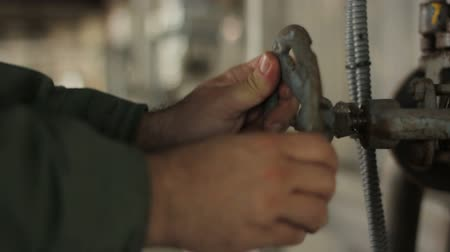 The hands turn the valve in the factory