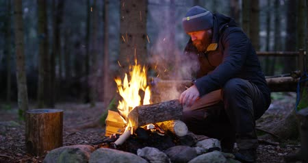 madeira : Adult man fires up campfire outdoor in the forest