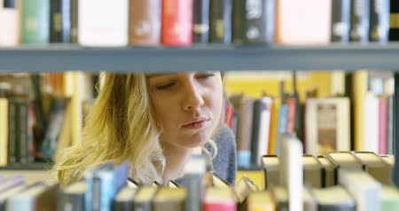 könyvtár : Young female student looking for book in school library
