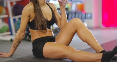 сильный : Close-up portrait of resting fitness woman sitting on the floor drinking water Стоковые видеозаписи