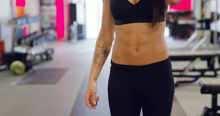 abs : Workout portrait of smiling woman with fit body drinks water in fitness gym