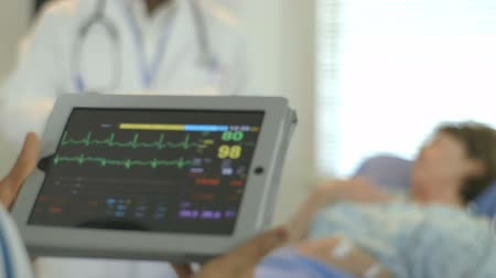 vital signs : Camera rack focuses from a portable patient monitor held by a doctor to a mature woman lying in a hospital bed. Stock Footage