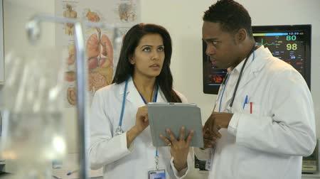 szpital : Focus moves from an IV bag solution in the foreground to two physicians discussing what they are studying on an electronic tablet pc. Wideo