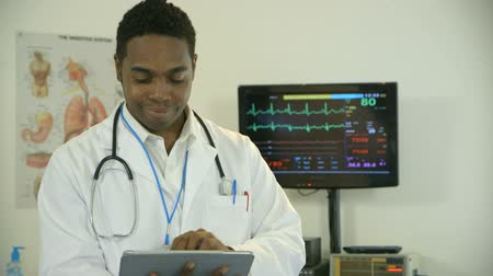 интерн : Young African American intern or physician goes looks up from what he is studying on an electronic tablet and smiles confidently. Стоковые видеозаписи
