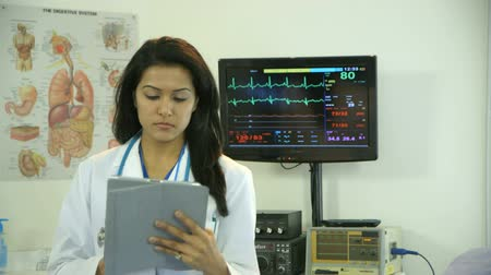 vital signs : A lovely physician of South Asian descent standing in a hospital room setting stops working on her electronic tablet looks up and smiles. Stock Footage
