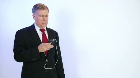 диалог : A mature businessman using earbuds and in-line mic to facilitate a cell phone conversation. Copy space, blue background