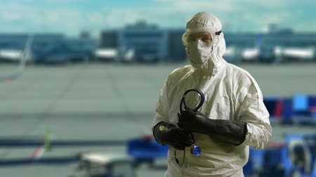 protective eyewear : A doctor wearing full protection against biological exposure such as to the Ebola virus in airport scene. Stock Footage