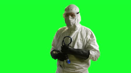 protective eyewear : A doctor or nurse wearing full protection against biological exposure such as to the Ebola virus on green screen background.