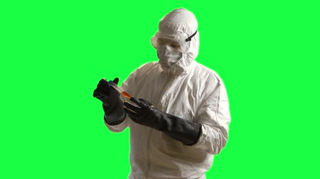 glove : green screen of a doctor in hazmat gear looking at a blood sample