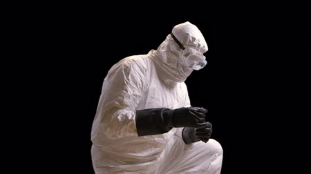 maszk : Doctor in hazmat gear in a dark room looking at a sample