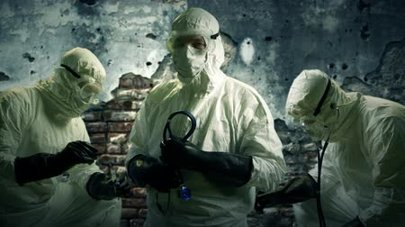 оборонительный : Three doctors or nurses wearing full protection against exposure to the Ebola virus working onsite with dilapidated wall in background. Стоковые видеозаписи