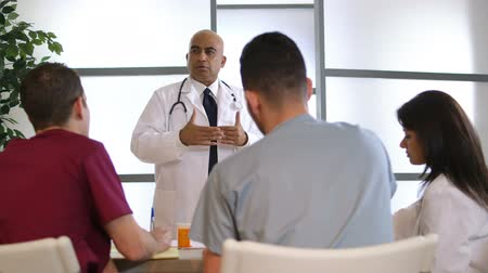egészségügy és az orvostudomány : An Indian physician stands in front of a small group of fellow doctors giving a talk. Canon C300