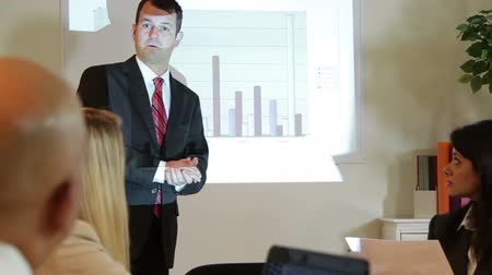 conferência : A businessman standing in front of an image protected on the wall by a projector presents the data to a group of colleagues.