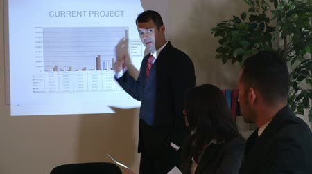 apresentação : A projector shines a graph on the screen and on a businessman explaining the information. Canon C300