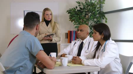 ügy : Lovely blond pharmaceutical saleswoman giving a presentation to a group of doctors sitting at a table. Canon C300 camera tracks around scene.