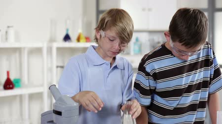 medir : Two young students in classroom lab working on a science project together.