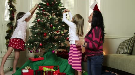 С Рождеством : A pretty mom and her two young daughters in the living room decorating a Christmas tree. Стоковые видеозаписи