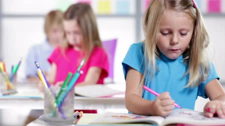 concentrando : A cute little girl in a classroom setting works diligently on her school task.