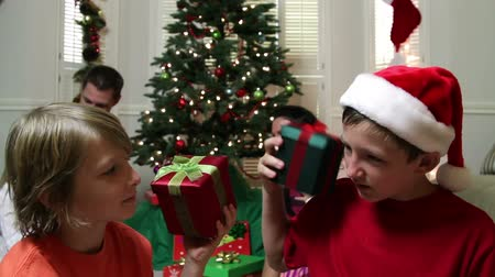 ailelerin : Two young boys in a family Christmas scene shake their presents as if trying to determine the contents. Stok Video