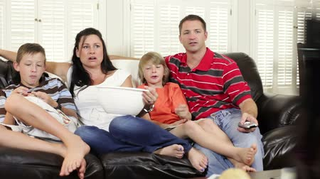 ailelerin : Mom and dad with their two boys sitting on a couch watch TV together. Camera dolly shot.
