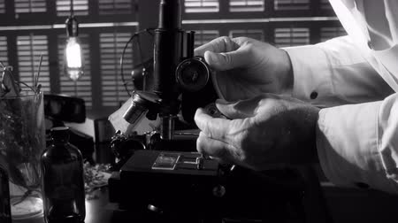 mikroskop : A botanist or biologist looking through an old microscope with other items in the scene that indicate the era is circa 1940. Dostupné videozáznamy