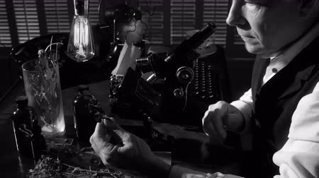 régi : A botanist or biologist looking through an old microscope with other items in the scene that indicate the era is circa 1940. Black and White 4K footage with dolly movement. Stock mozgókép