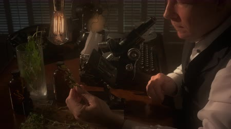 régi : A botanist or biologist looking through an old microscope with other items in the scene that indicate the era is circa 1940. Black and white footage with dolly movement. Stock mozgókép