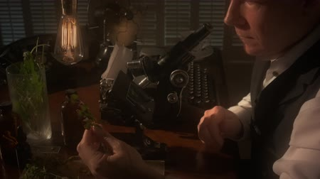 ajustando : A botanist or biologist looking through an old microscope with other items in the scene that indicate the era is circa 1940. Black and white footage with dolly movement. Stock Footage