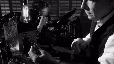 naukowiec : A botanist or biologist looking through an old microscope with other items in the scene that indicate the era is circa 1940. Black and white footage with dolly movement. Wideo