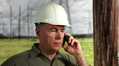 utilidade : An electrical power grid repairman on the phone and smiles at camera.