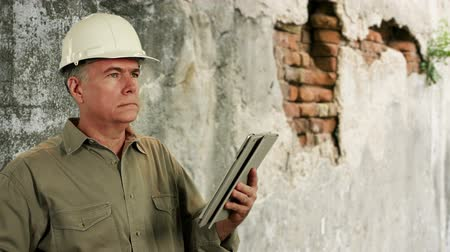 deneyimli : Man in hardhat with old brick wall in background using electronic tablet. Stok Video
