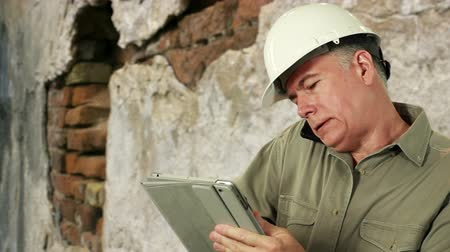 deneyimli : Man in hardhat with old brick wall in background engaged in cell phone conversation while using electronic tablet.