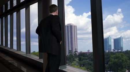 interiér : A businessman looking out the large plate glass windows of a long skywalk turns and smiles with satisfaction.